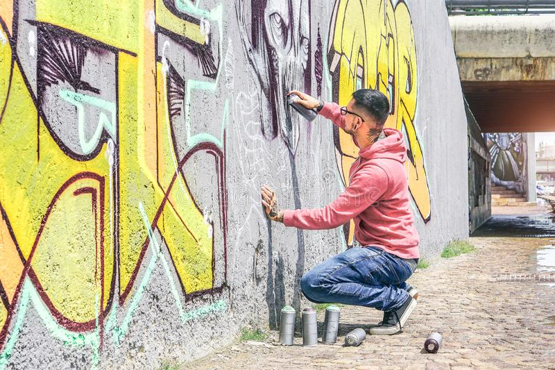 街道街道画与颜色喷壶的艺术家绘画在墙壁上的一张黑暗的妖怪头骨街道画在室外的城市 免版税库存照片