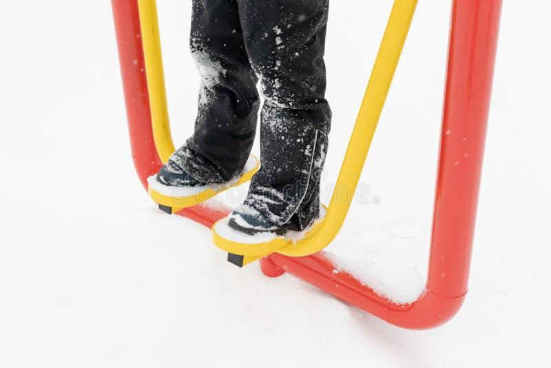 街道锻炼设备在冬天、户外运动健身和体型 做锻炼锻炼的无法认出的人室外 免版税库存照片
