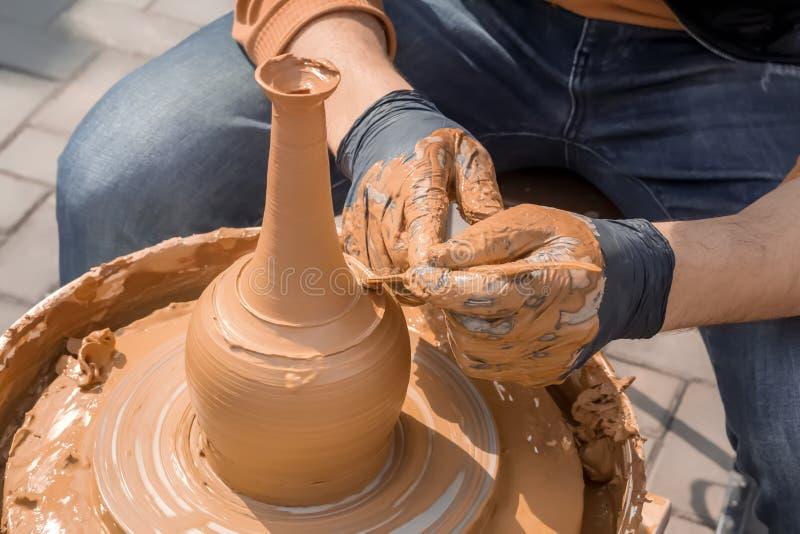 街道陶瓷工做一个花瓶黏土在横式转盘 库存照片
