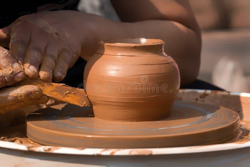 街道陶瓷工的手在横式转盘做一个泥罐 库存图片