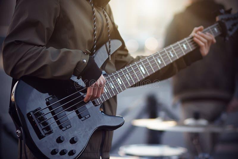 街道音乐家在五串电吉他使用 库存图片