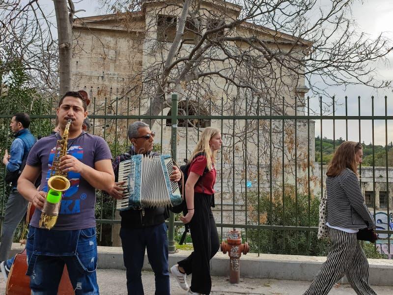 街道音乐家在Adrianou Steet演奏音乐在蒙纳斯提拉奇作为游人通过与Attalos纪念碑Stoa在backgorund的 免版税库存图片