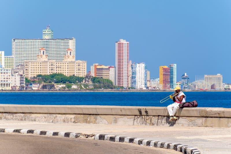街道音乐家播放伸缩喇叭在著名malecon墙壁在哈瓦那 库存图片