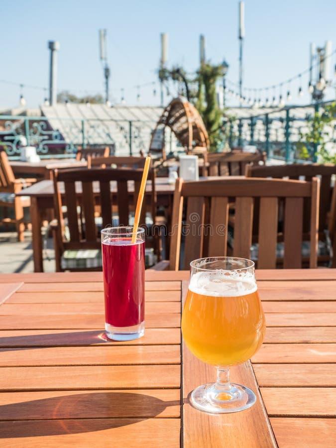 街道食物和饮料,任命概念 一杯莓果汁和一杯在一张木桌上的新鲜的啤酒 免版税库存图片