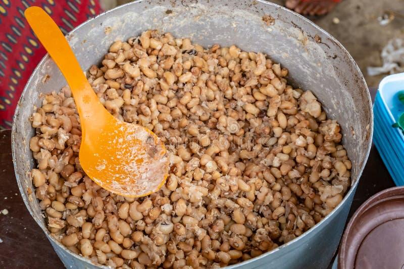 街道食物在拉各斯尼日利亚;有匙子的Ewa Agoyin在罐 库存图片