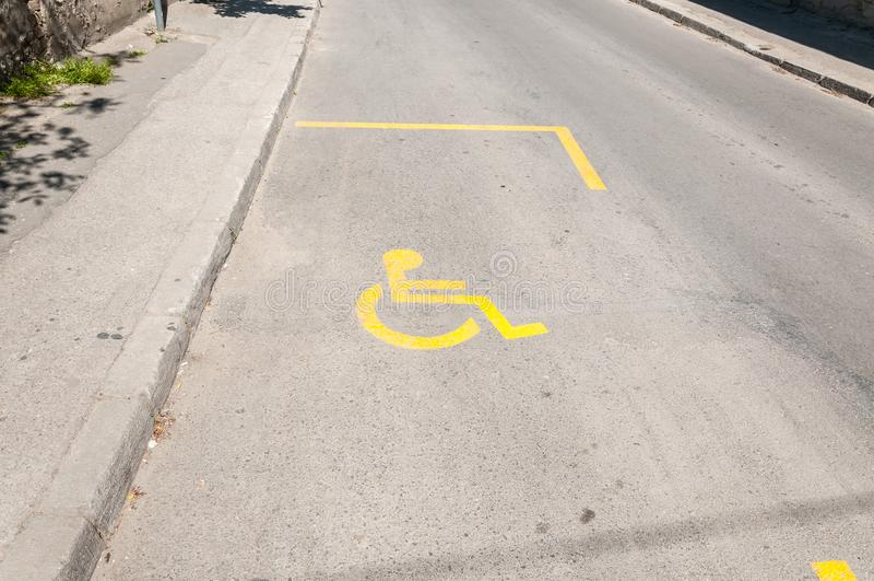 街道驾驶有无效轮椅的黄色标志或标志的汽车的残疾人的停车位 库存图片