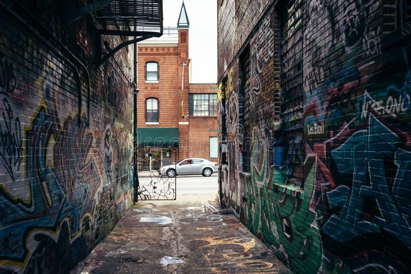 街道画胡同和霍华德街在巴尔的摩,马里兰 库存照片