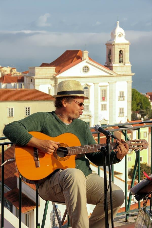 街道Alfama处所的吉他演奏员。里斯本。葡萄牙 免版税库存照片