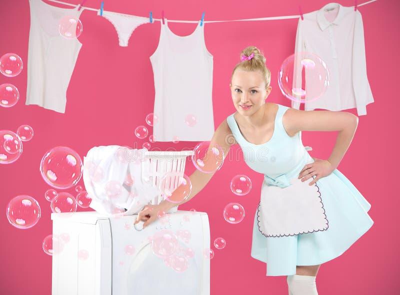 洗衣店,垂悬,排序-跑在房子附近的愉快的妇女。 免版税库存照片