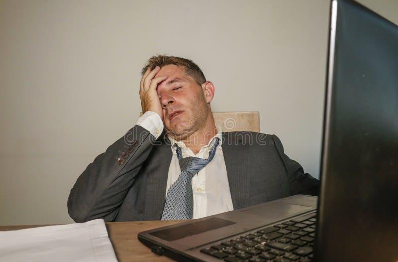 衣服和领带工作的年轻沮丧和被注重的商人被淹没在办公室手提电脑书桌遭受的头疼 库存照片