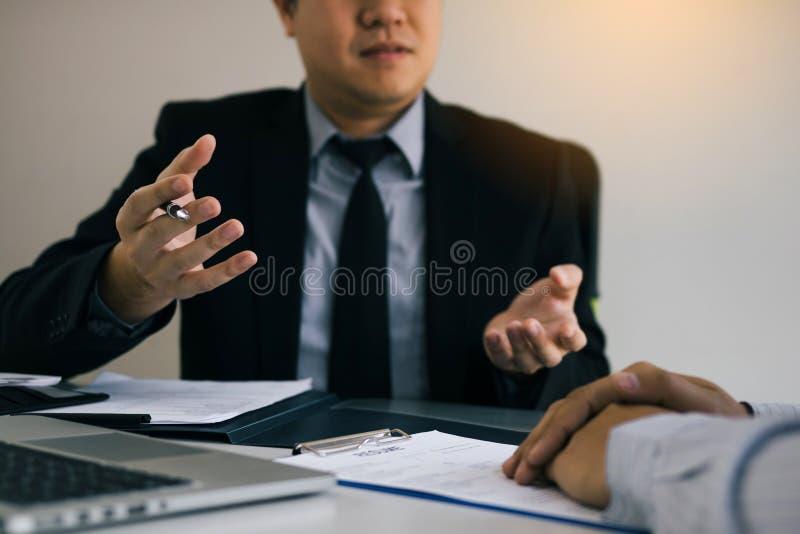 衣服执行委员的精明的商人专业人打手势和谈话在会见关于工作的雇员在现代办公室 库存图片
