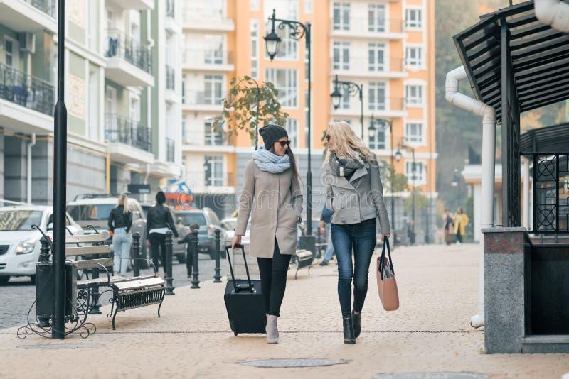 衣服暖和的两年轻微笑的美女步行沿着向下带着旅行手提箱,谈话的妇女的城市街道的笑和 免版税库存照片