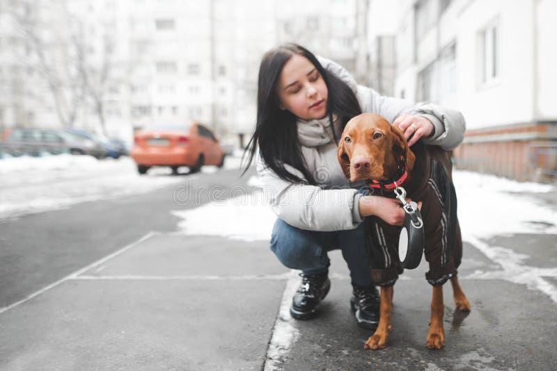 衣服暖和的妇女坐与狗的地面并且调整在街道的背景的衣领 免版税库存照片