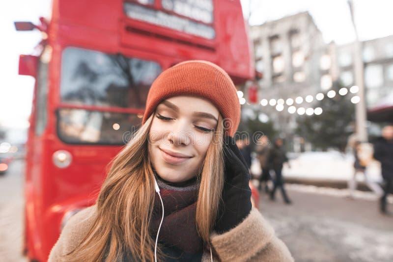 衣服暖和的微笑的女孩在街道引人注意在一个冬日,听在耳机的音乐有她的闭上的眼睛的 画象 免版税库存照片
