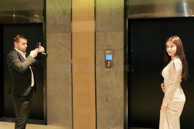 衣服照片的人在智能手机美女 免版税库存图片
