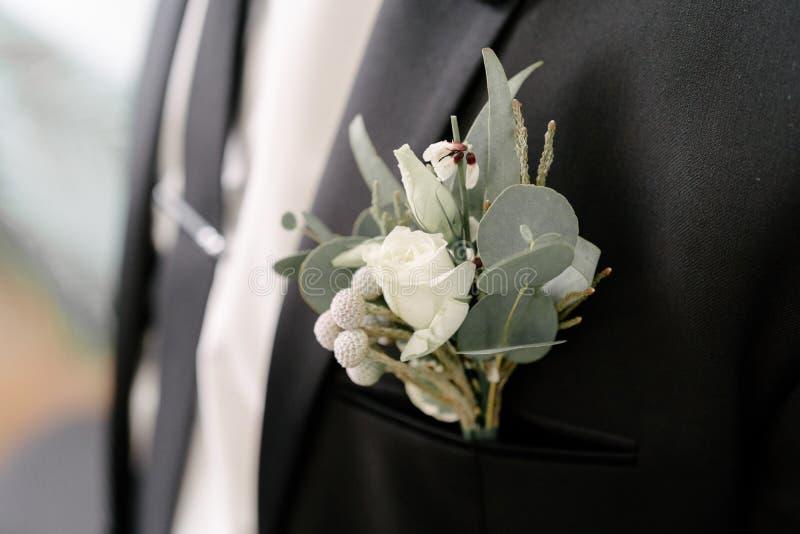 衣服的一个人调直他的在他的夹克的钮扣眼上插的花 免版税库存照片