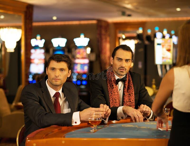 衣服的两个人在赌博的桌后 免版税库存照片