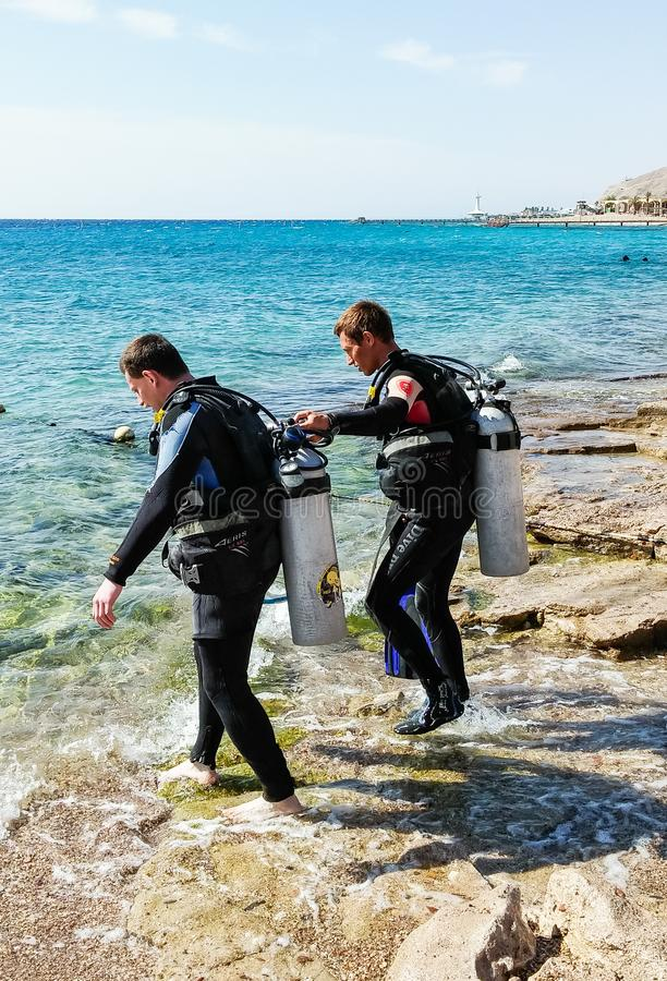 衣服的两名轻潜水员佩戴水肺的潜水的去水在埃拉特市附近在以色列 免版税图库摄影
