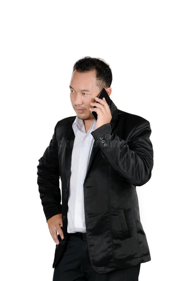 衣服的亚裔商人谈话在手机孤立 免版税图库摄影