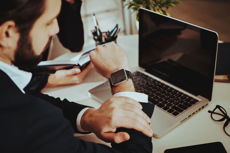 衣服的人与膝上型计算机和计划的时间一起使用 库存图片