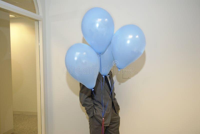 衣服的人在气球后 免版税库存图片