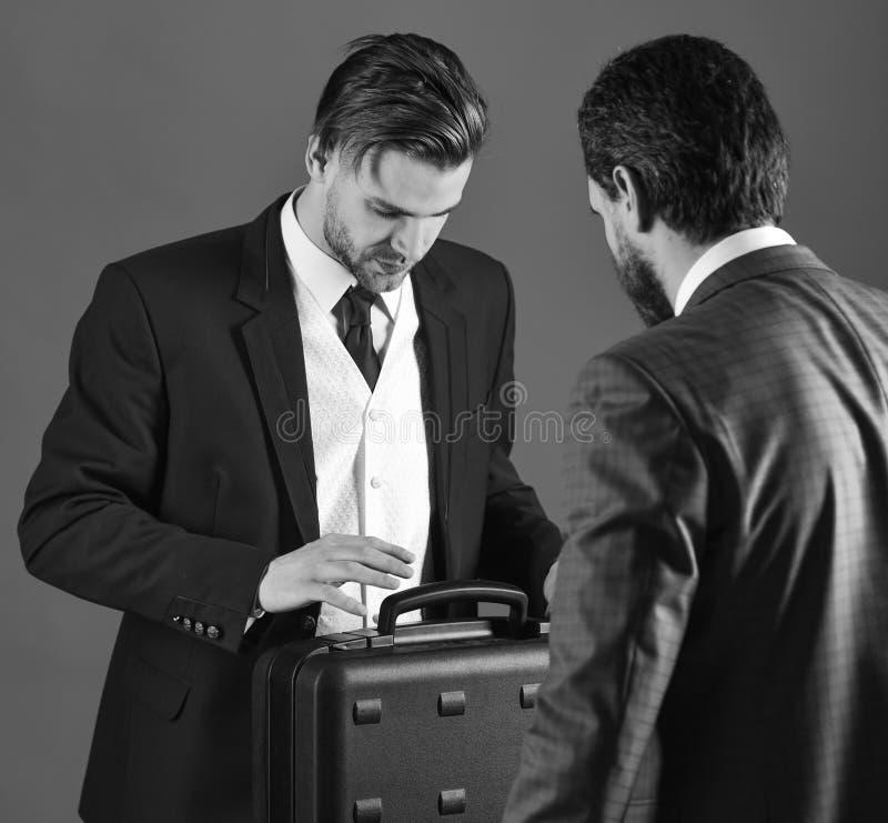 衣服的人或商人为黑公文包移交见面 有繁忙的面孔的商务伙伴在蓝色背景 免版税库存照片