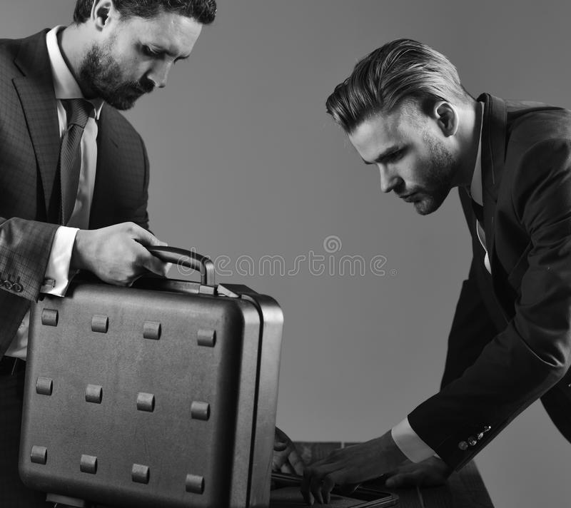 衣服的人或商务伙伴为交换见面或成交 商人提供非法交易或贿款 事务 图库摄影