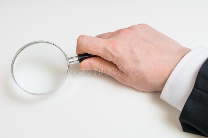 衣服的人拿着放大镜 背景查出的白色 免版税库存照片