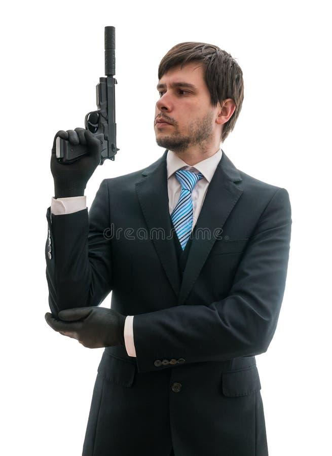衣服的人拿着有遏声器的手枪手中 背景查出的白色 免版税库存图片