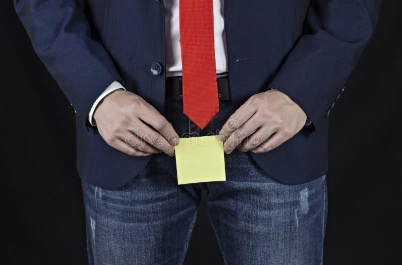 衣服的人,商人在他的鼠蹊区域的拿着贴纸,黑背景,前列腺炎 免版税库存照片