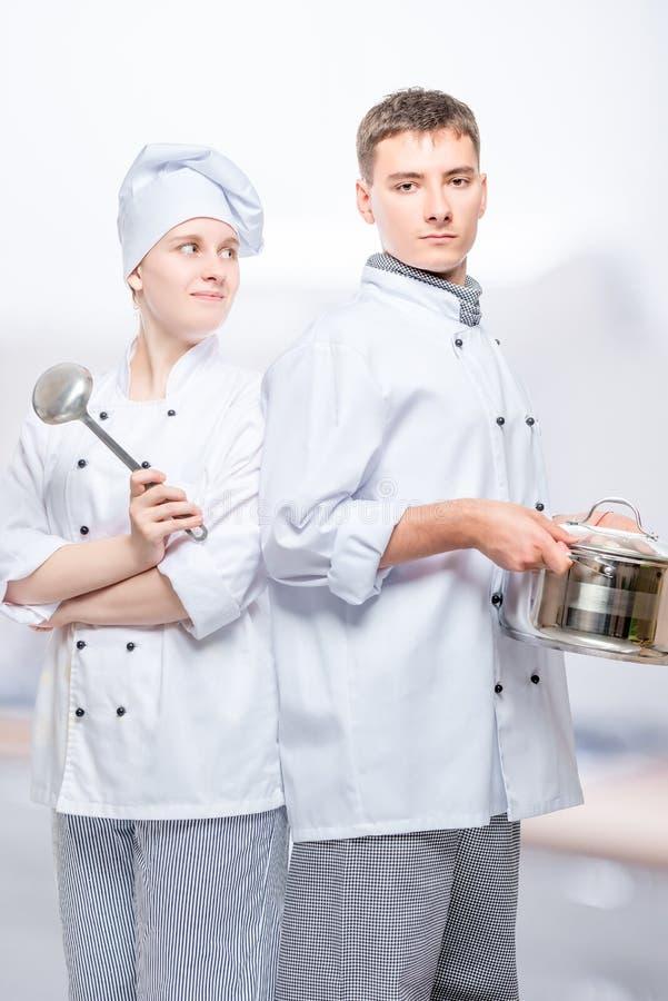 衣服的厨师与摆在反对背景的平底深锅和杓子 免版税库存照片