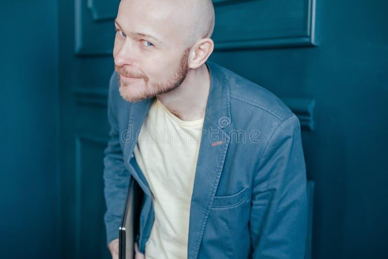 衣服的可爱的成人成功的秃头有胡子的人与狡猾膝上型计算机神色到照相机里和微笑在蓝色墙壁背景 库存图片