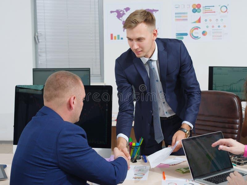 衣服的商人,在办公室握手 免版税图库摄影