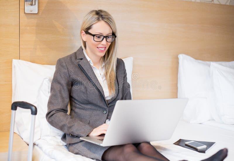 衣服的女商人坐在床上和与计算机一起使用在旅馆客房 库存照片