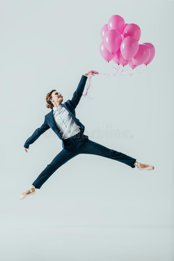 衣服的女实业家和跳跃与桃红色气球的芭蕾舞鞋 免版税图库摄影