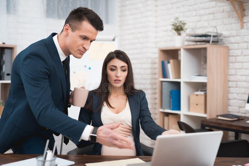 衣服的年轻不悦的人责骂差错的怀孕的女孩在被完成的工作 库存照片
