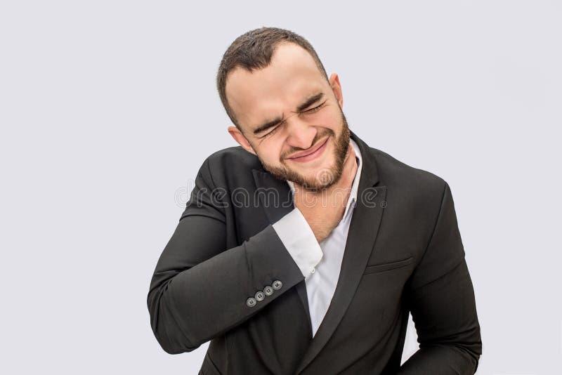 衣服的年轻人遭受喉咙痛 他握在脖子和抽缩的手 人保持眼睛闭上 查出在白色 免版税库存照片
