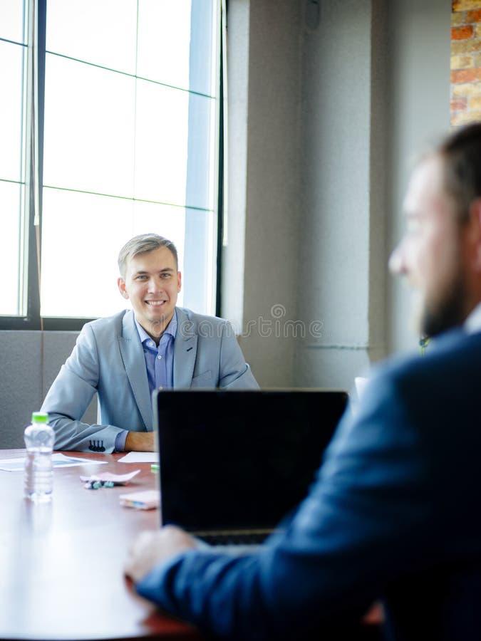 衣服的年轻人,在书桌在办公室 特写镜头 免版税库存图片