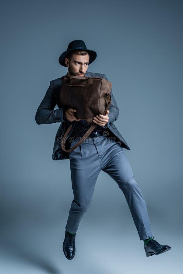 衣服的年轻英俊的拿着一个皮包的人和帽子喜欢 库存图片