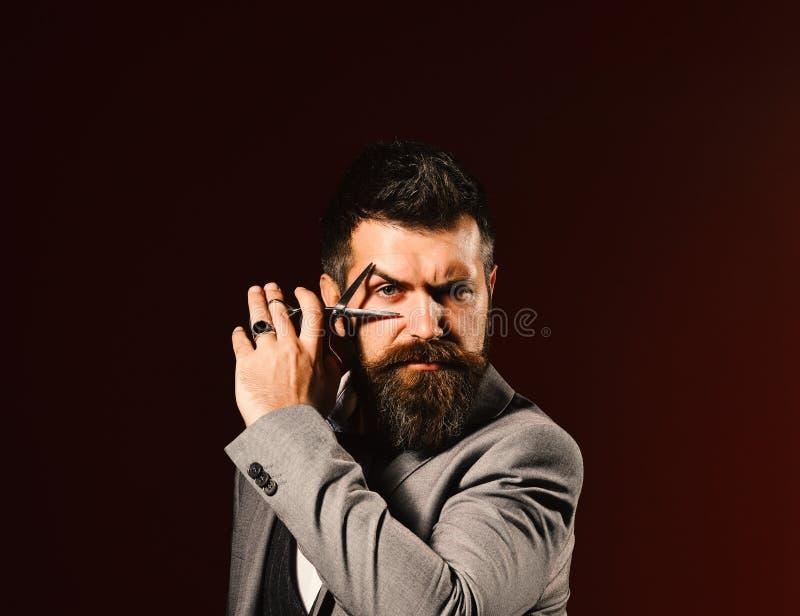 衣服的强壮男子假装切开眼睛 事务和理发店 免版税图库摄影