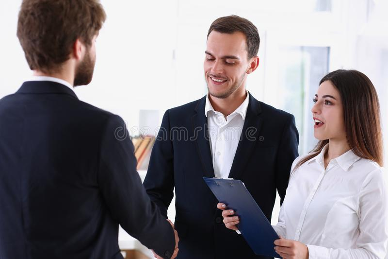 衣服的微笑的人在办公室握手你好 免版税库存图片