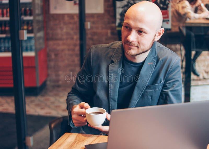 衣服的微笑的可爱的成人成功的秃头有胡子的人与在咖啡馆的膝上型计算机 免版税图库摄影