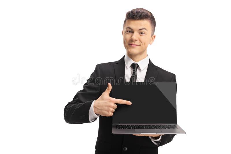 衣服的微笑的年轻人指向膝上型计算机的 免版税库存图片