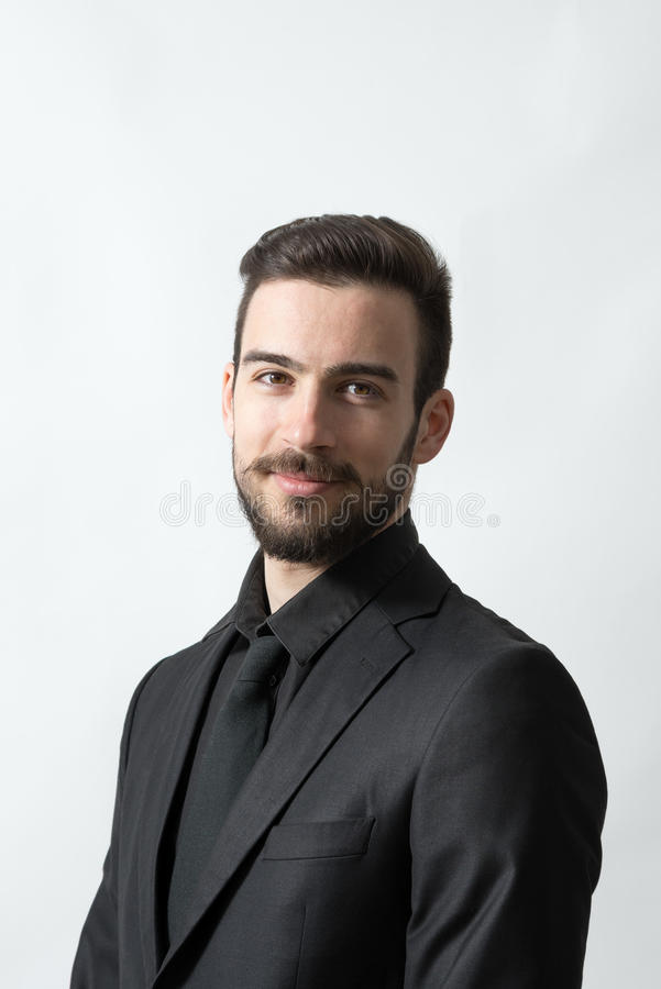 黑衣服的微笑的愉快的年轻有胡子的典雅的人 图库摄影