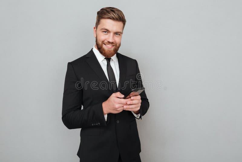 衣服的微笑的有胡子的人使用他的智能手机 免版税库存照片