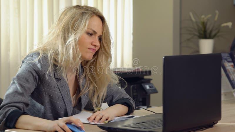 衣服的恼怒的女商人工作在计算机在办公室 免版税图库摄影
