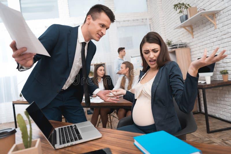 衣服的恼怒的年轻人对怀孕的女孩尖叫在办公室 怀孕在工作 免版税库存照片