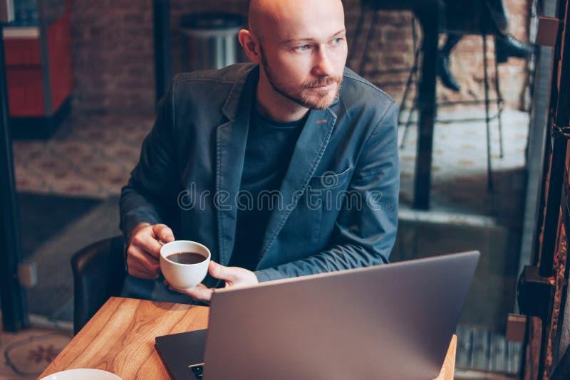 衣服的想法的可爱的成人成功的秃头有胡子的人与在咖啡馆的膝上型计算机 免版税图库摄影
