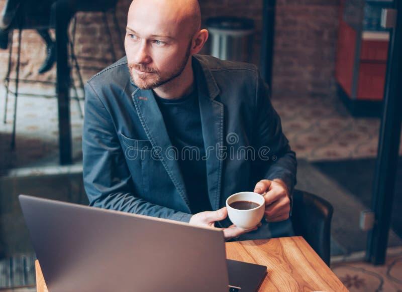 衣服的想法的可爱的成人成功的秃头有胡子的人与在咖啡馆的膝上型计算机 库存照片