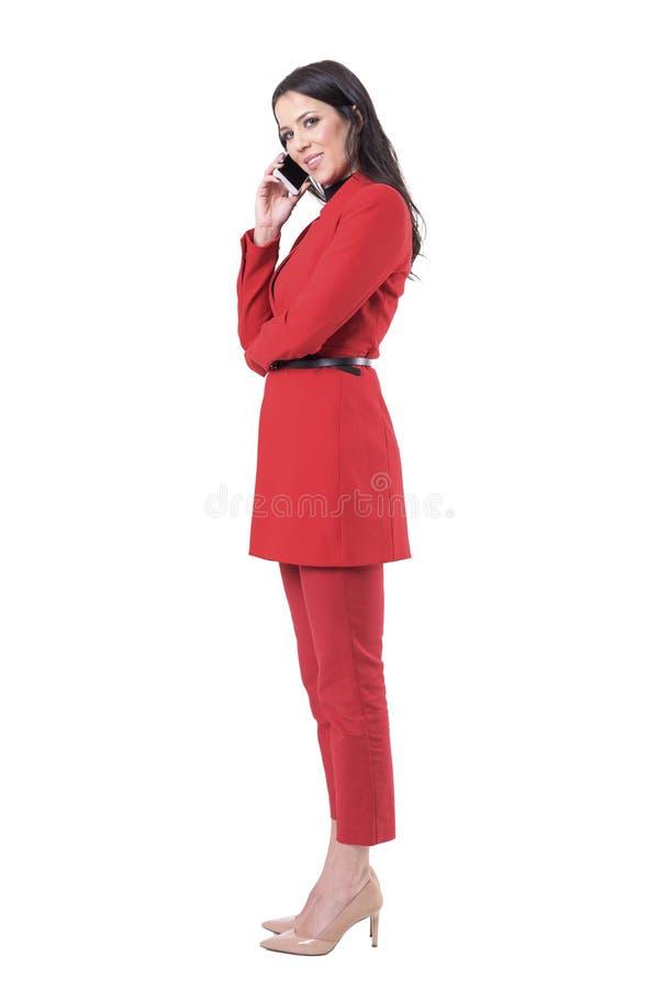 衣服的成功的确信的愉快的女商人有电话微笑和看照相机的 免版税库存图片
